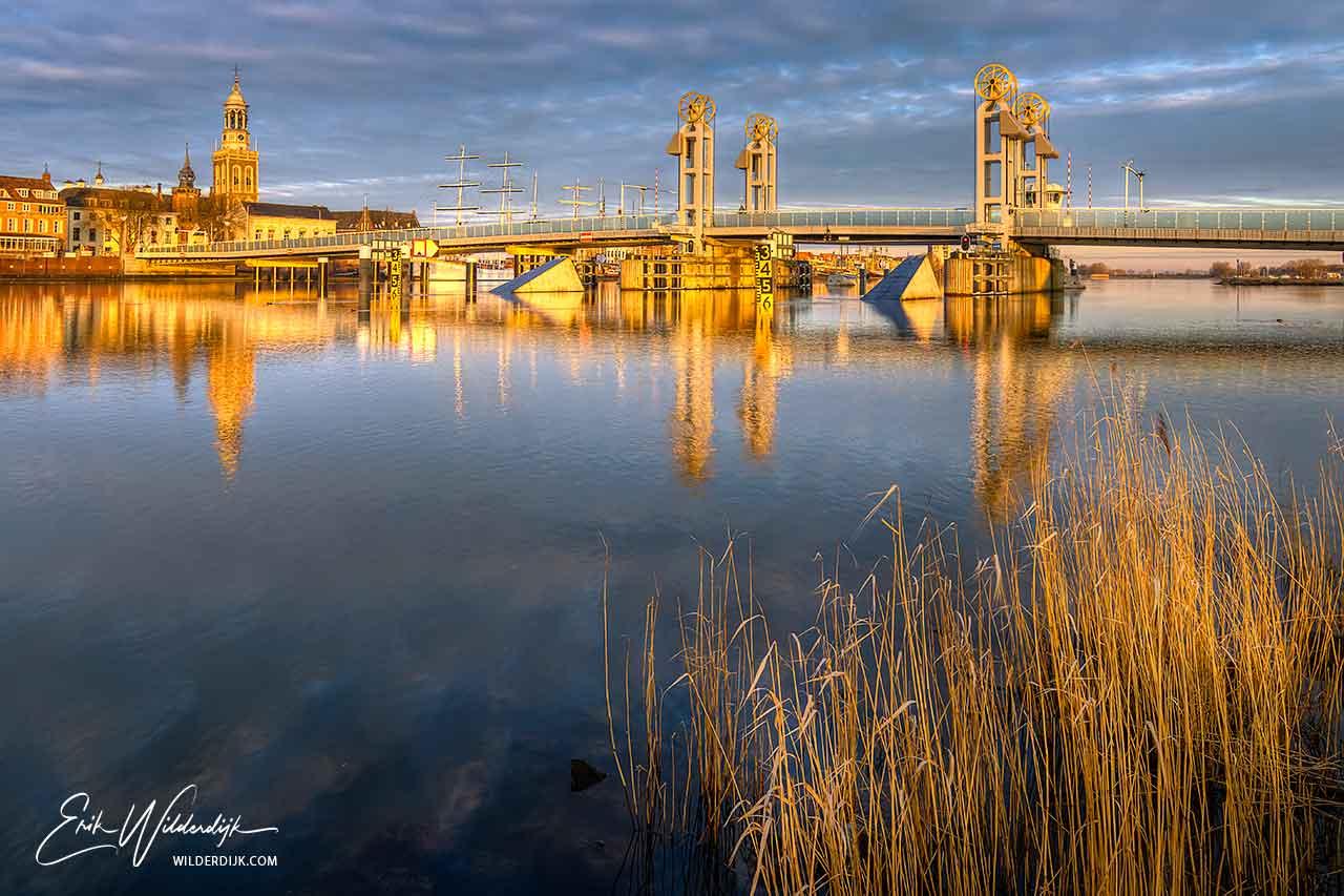 Het IJsselfront van Kampen met de stadsbrug en Nieuwe Toren in het gouden zonlicht direct na zonsopkomst